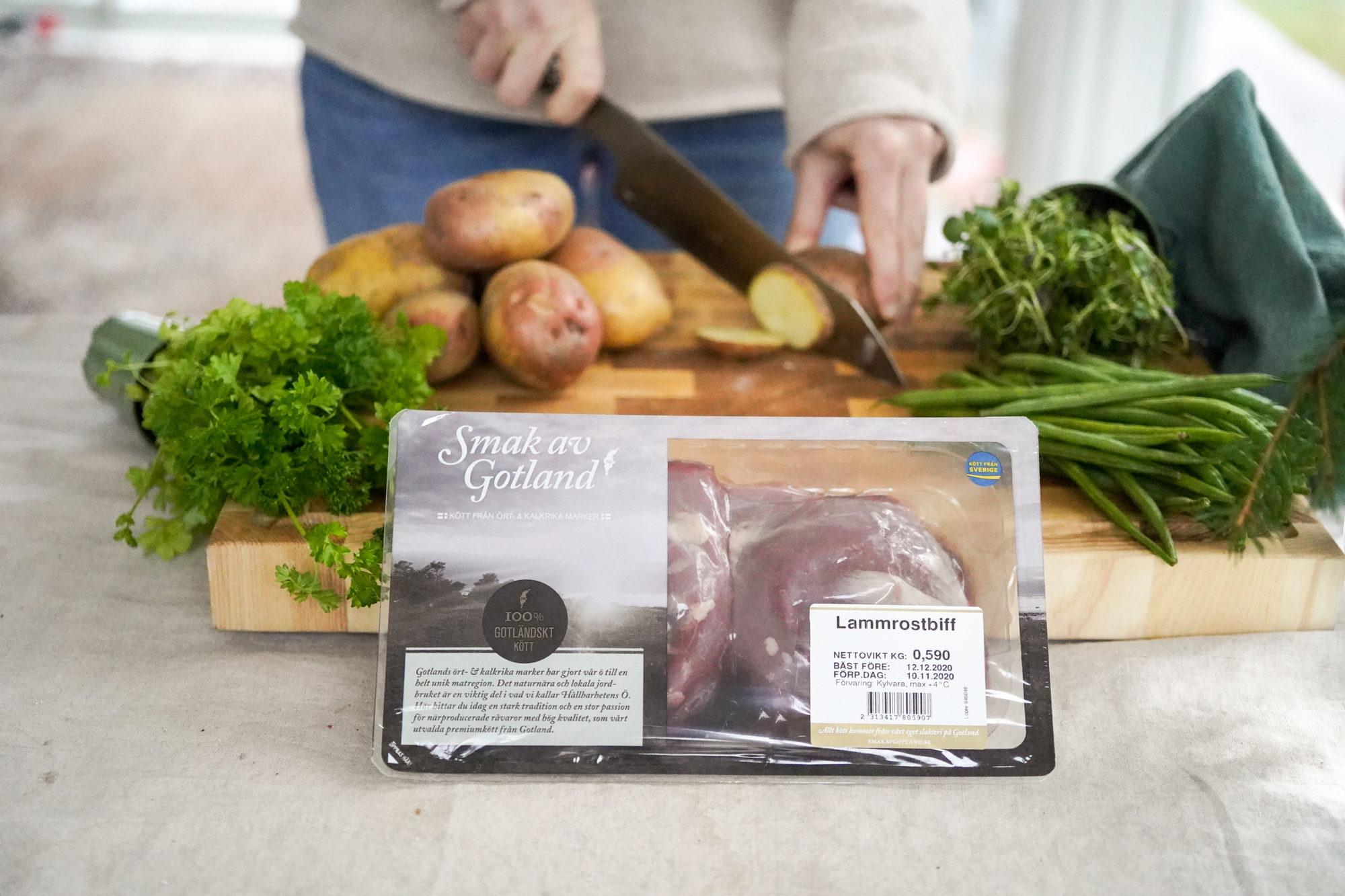Förpackning med lammrostbiff samt person som skärm potatis och örter i bakgrunden