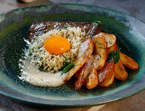Ett fat med en köttbit, potatis och sås toppat med en äggula