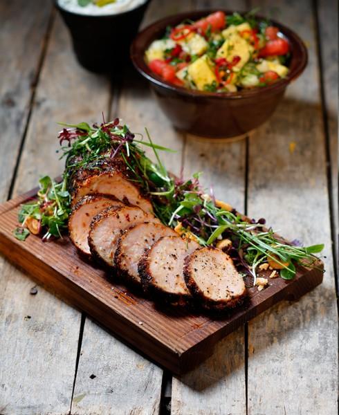 En bricka med skivor av kött med sallad runt om