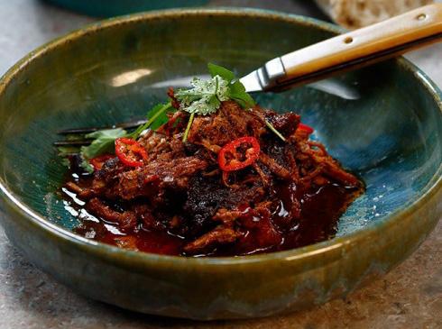 En skål serverad med pulled pork toppad med örter och chili